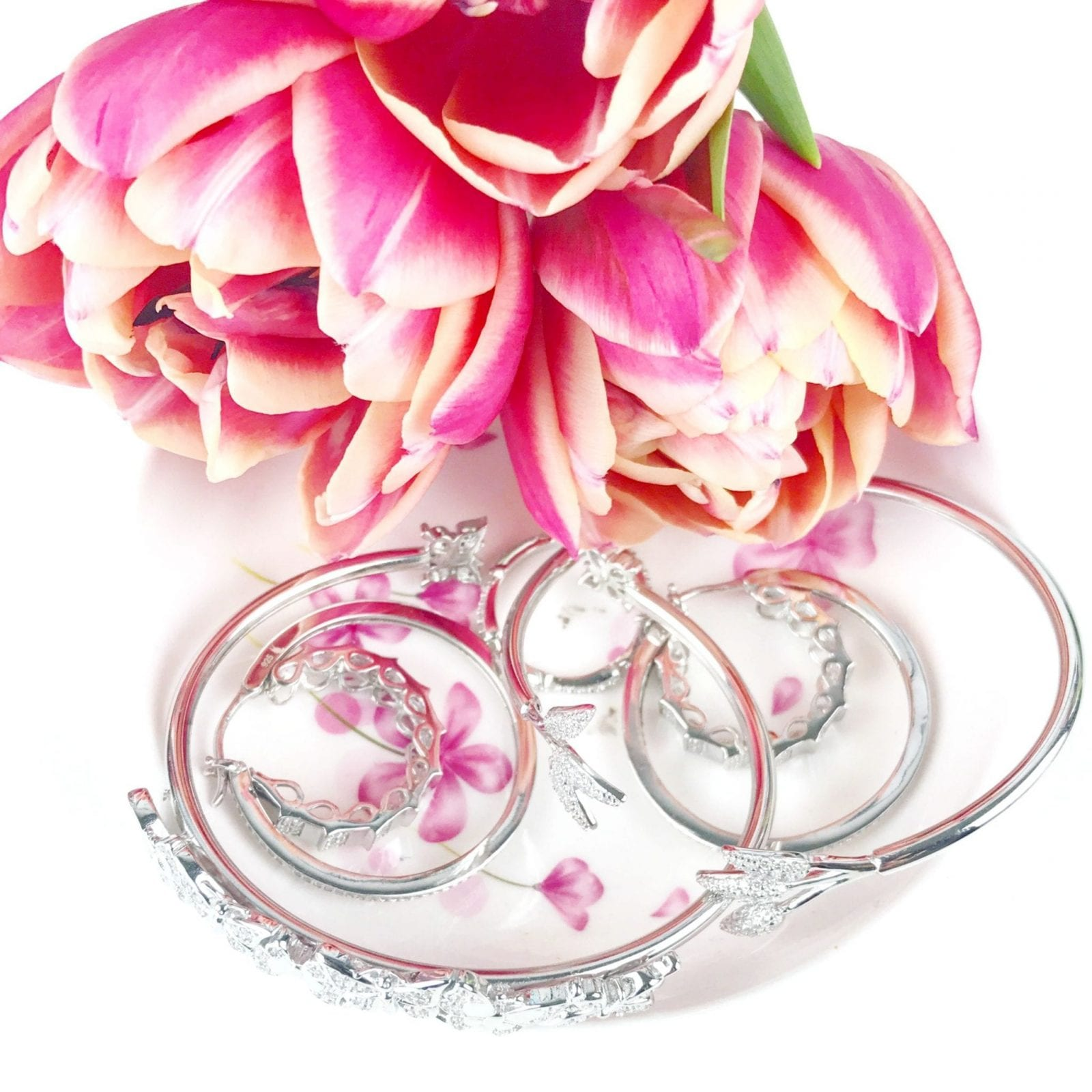 This is a close up of jewelry on a gorgeous floral plate.
