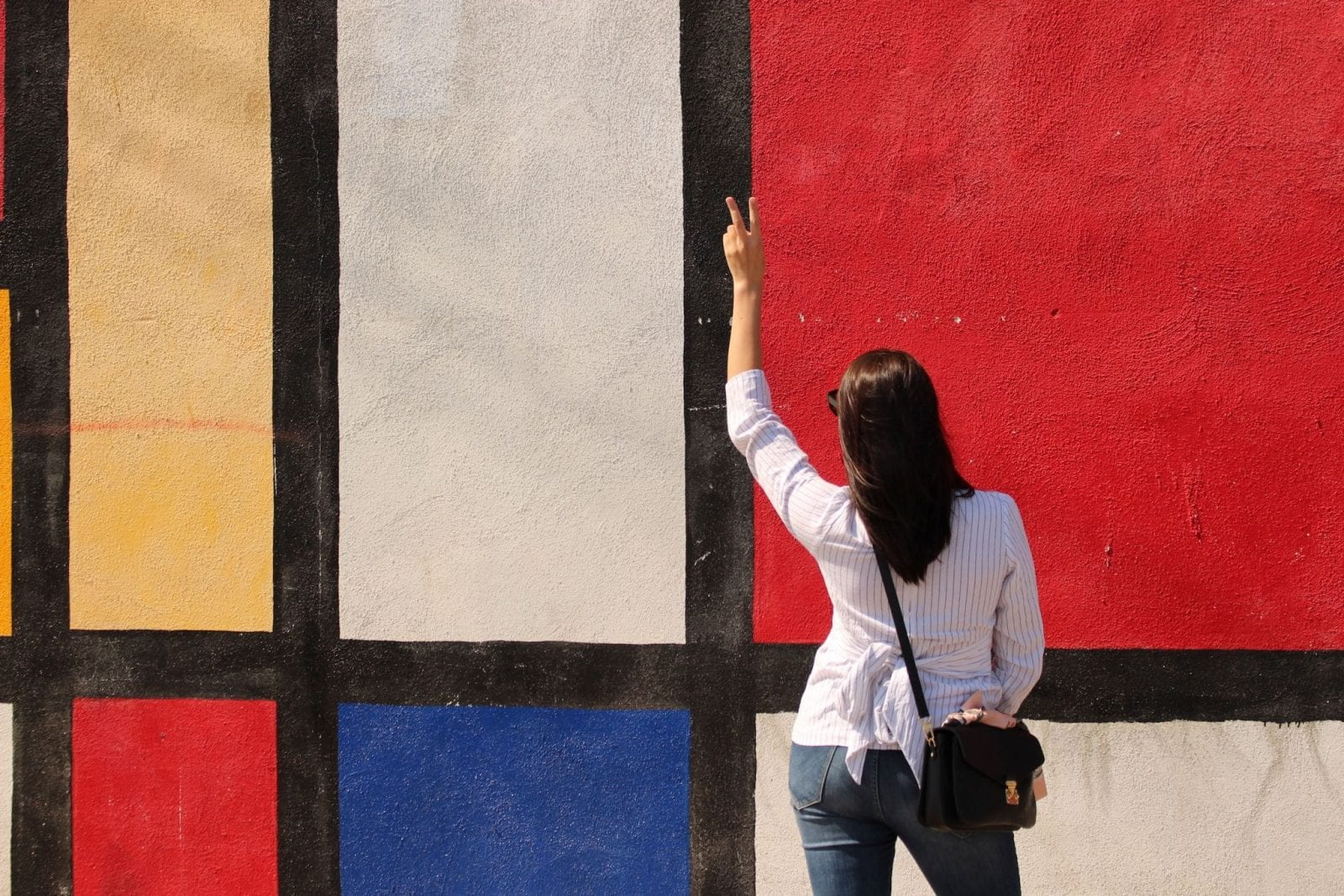 This is a photo of me against the Mondrian Wall in Los Angeles, holding up the peace sign.