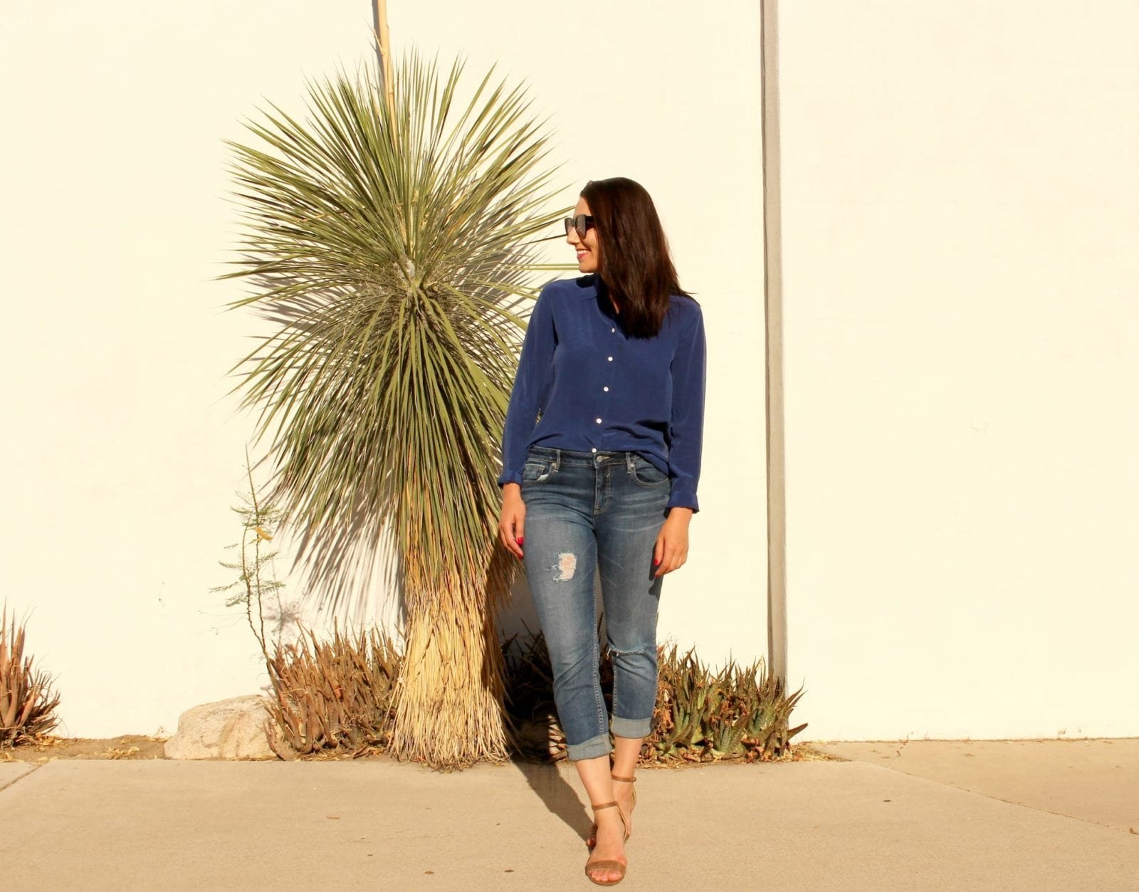 Standing looking to the right in my Everlane blouse and slightly distressed jeans.