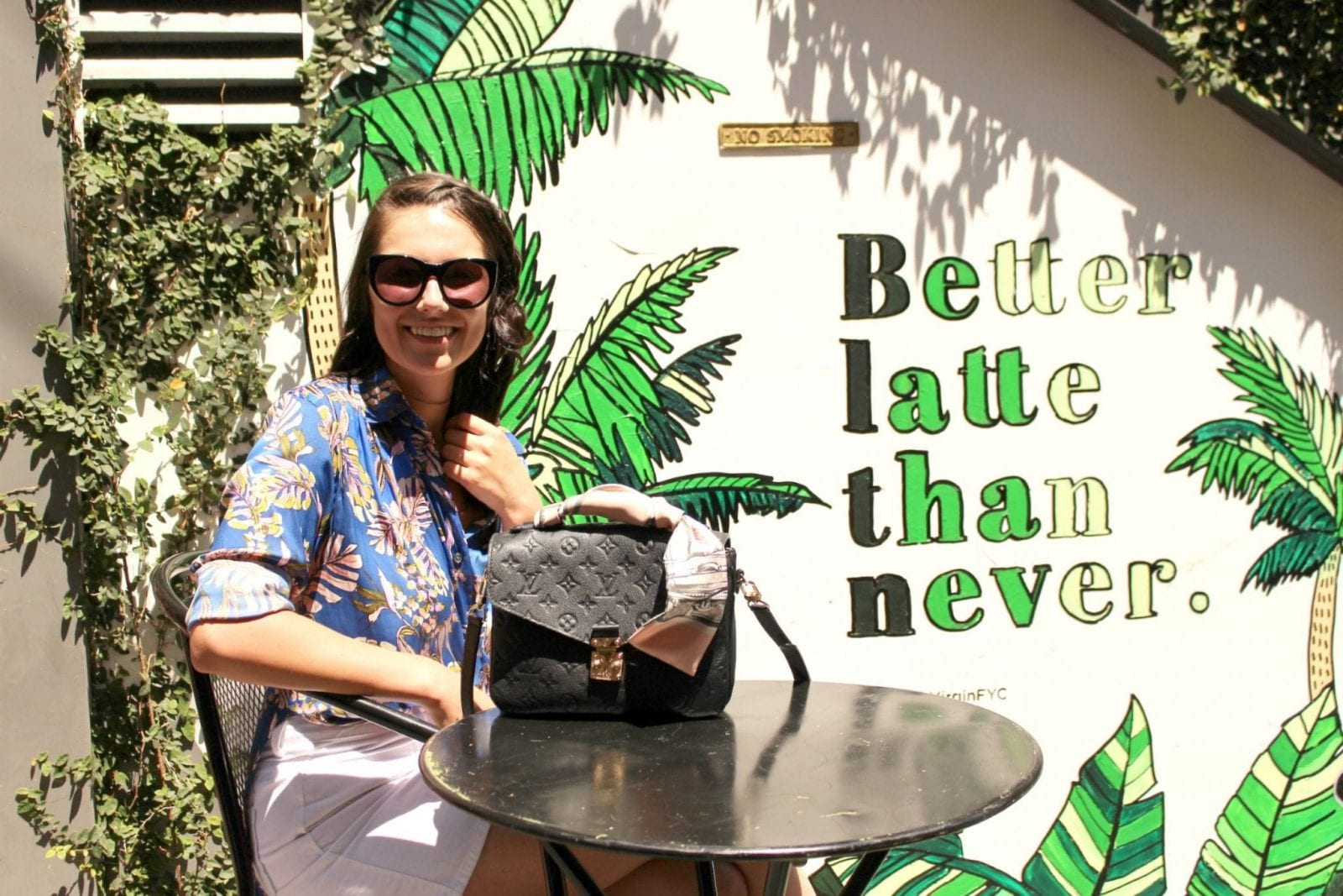 This is a photo of me sitting and smiling at a coffee table with my hawaiian shirt and my Louis Vuitton bag in Los Angeles.