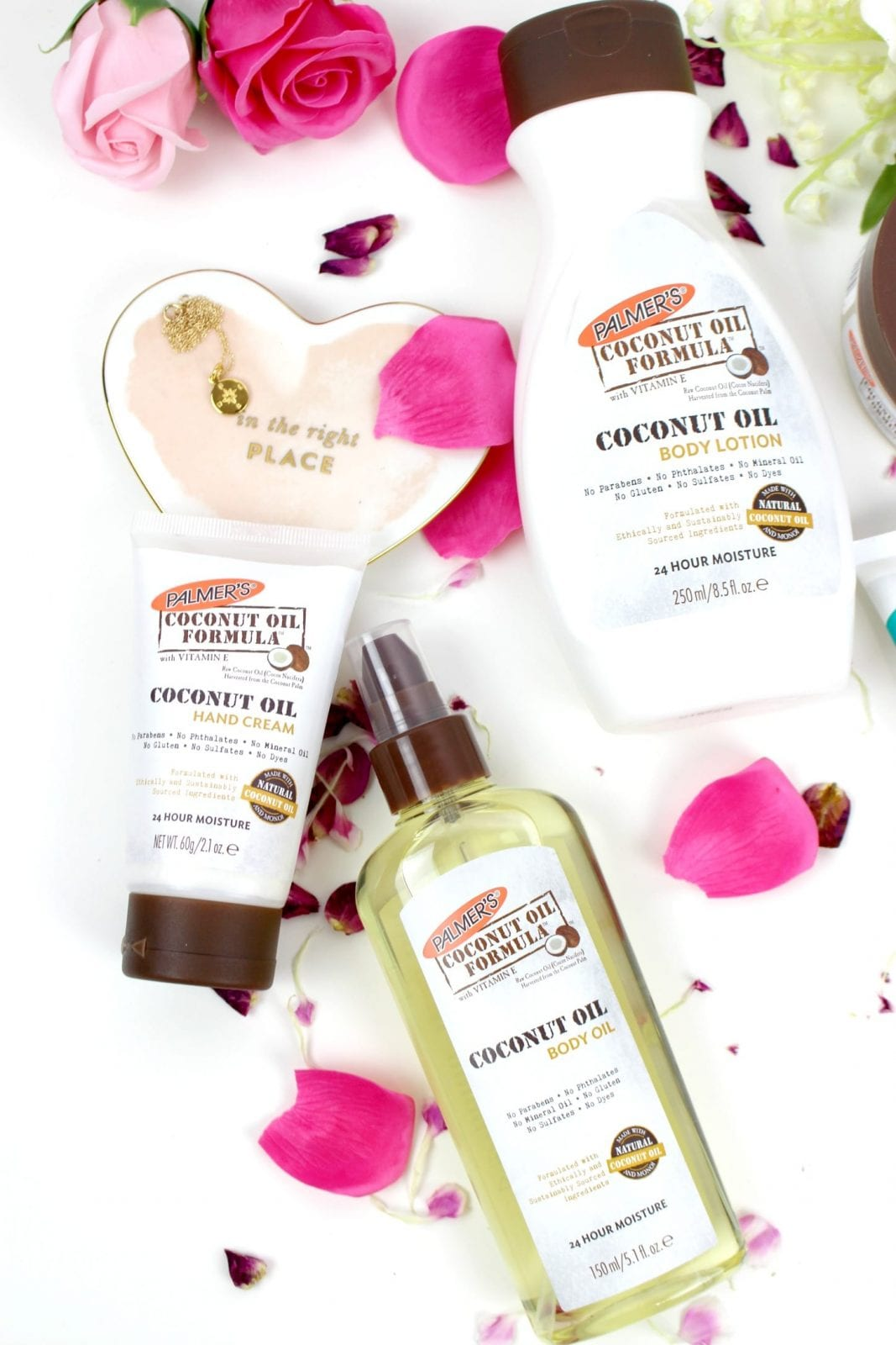 This is a close up of the Palmers Coconut Oil products, surrounded by pink rose petals.