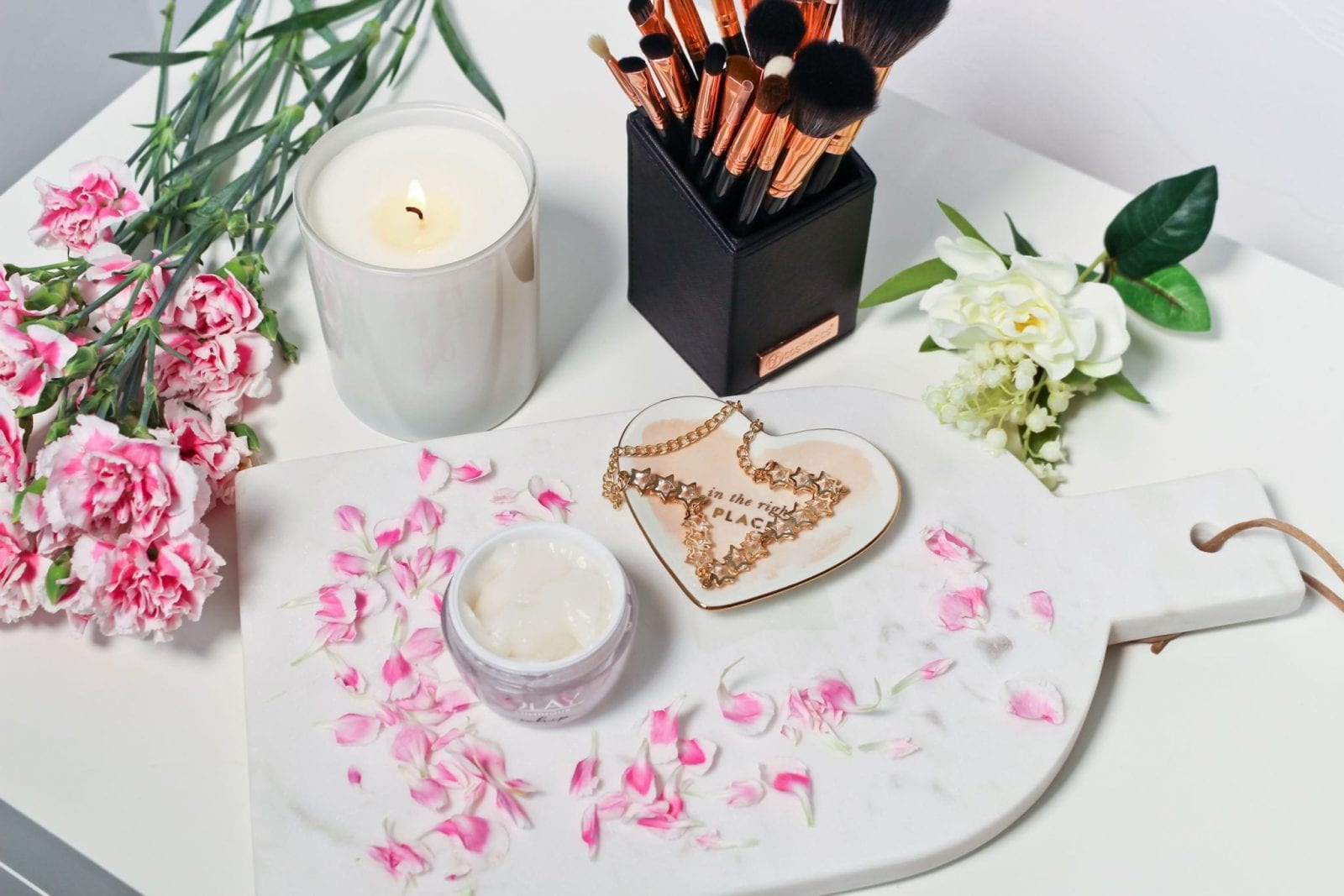 This is a flat lay shot of the Olay Whips Moisturizer, along with other pretty items like a necklace, pink flowers and such.