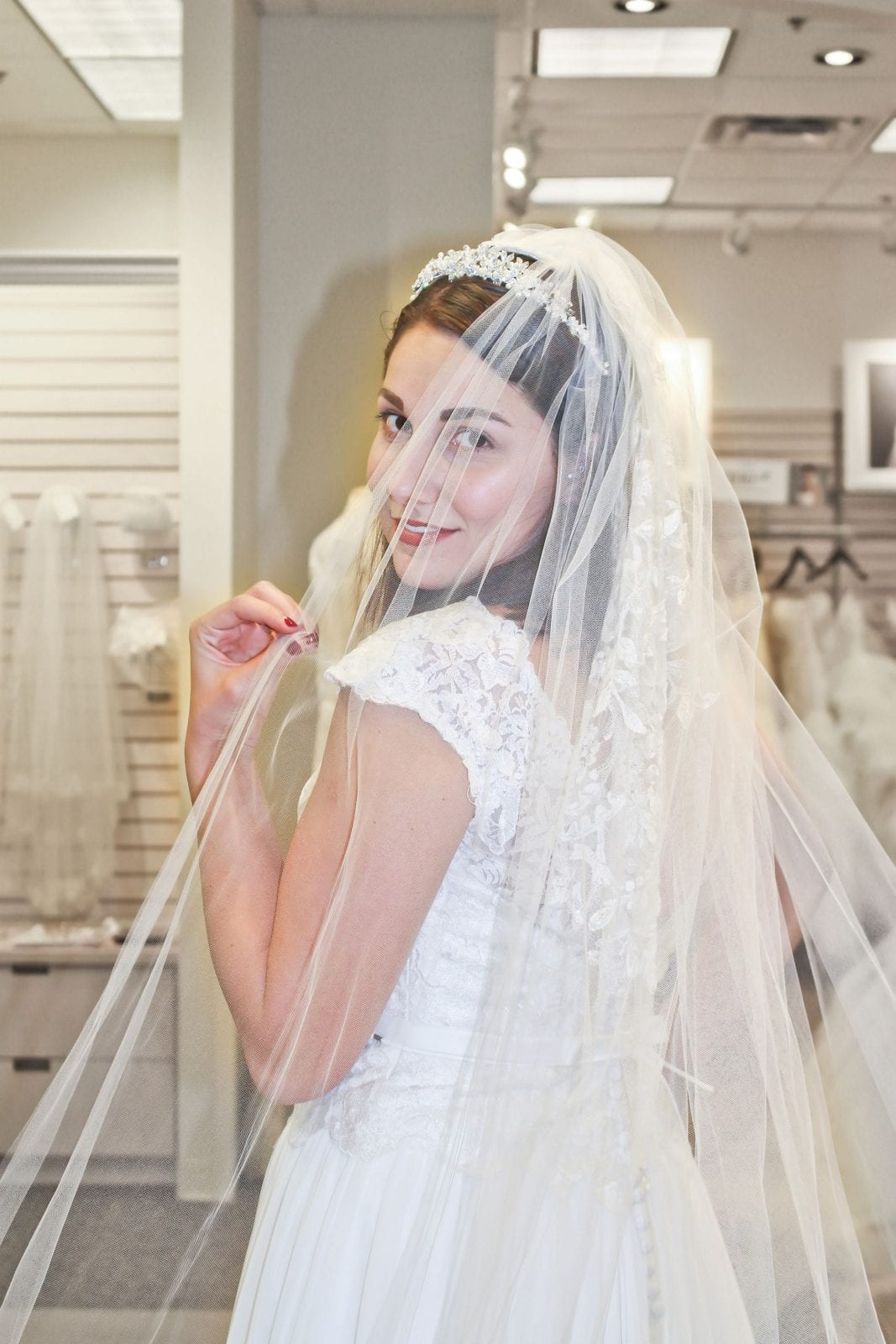 This is a close up of me looking back through a veil wearing a beautiful wedding dress from David's Bridal.