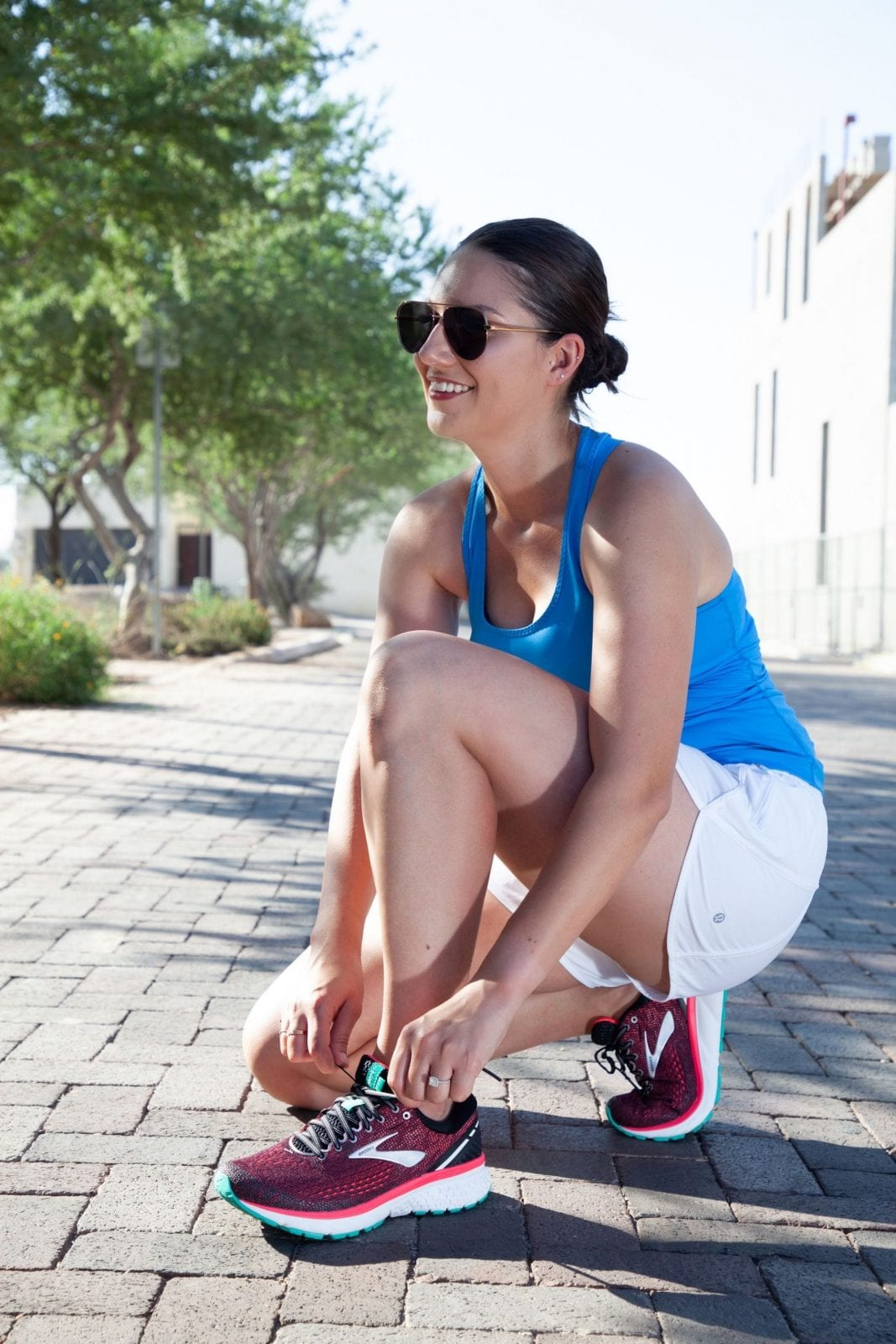 This is a full body shot of me bent over tying my Brooks Ghost 11 shoes, while smiling into the distance in my running gear.