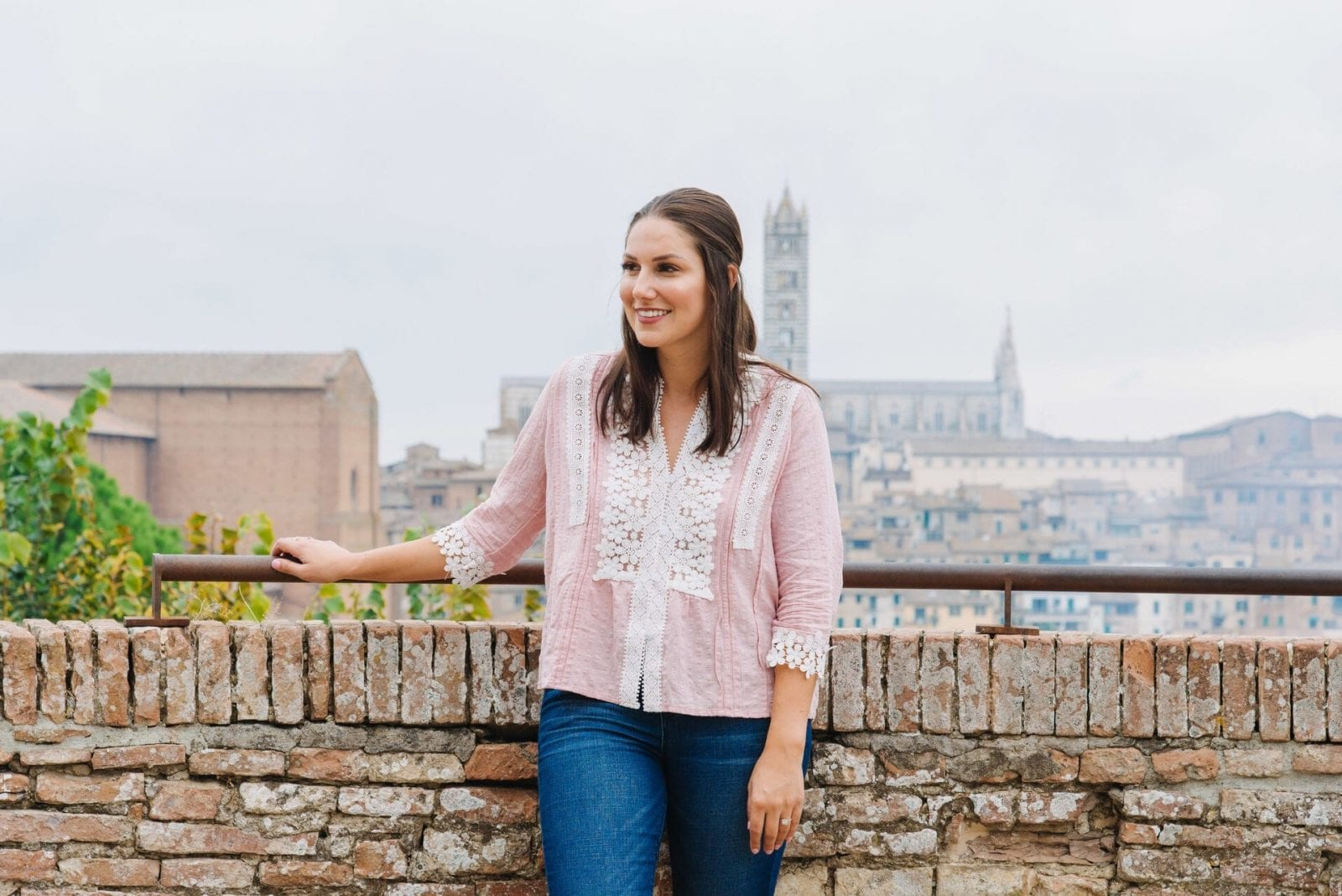 This is a close up of photo of me standing in a pink shirt, with a beautiful Siena view in the background.