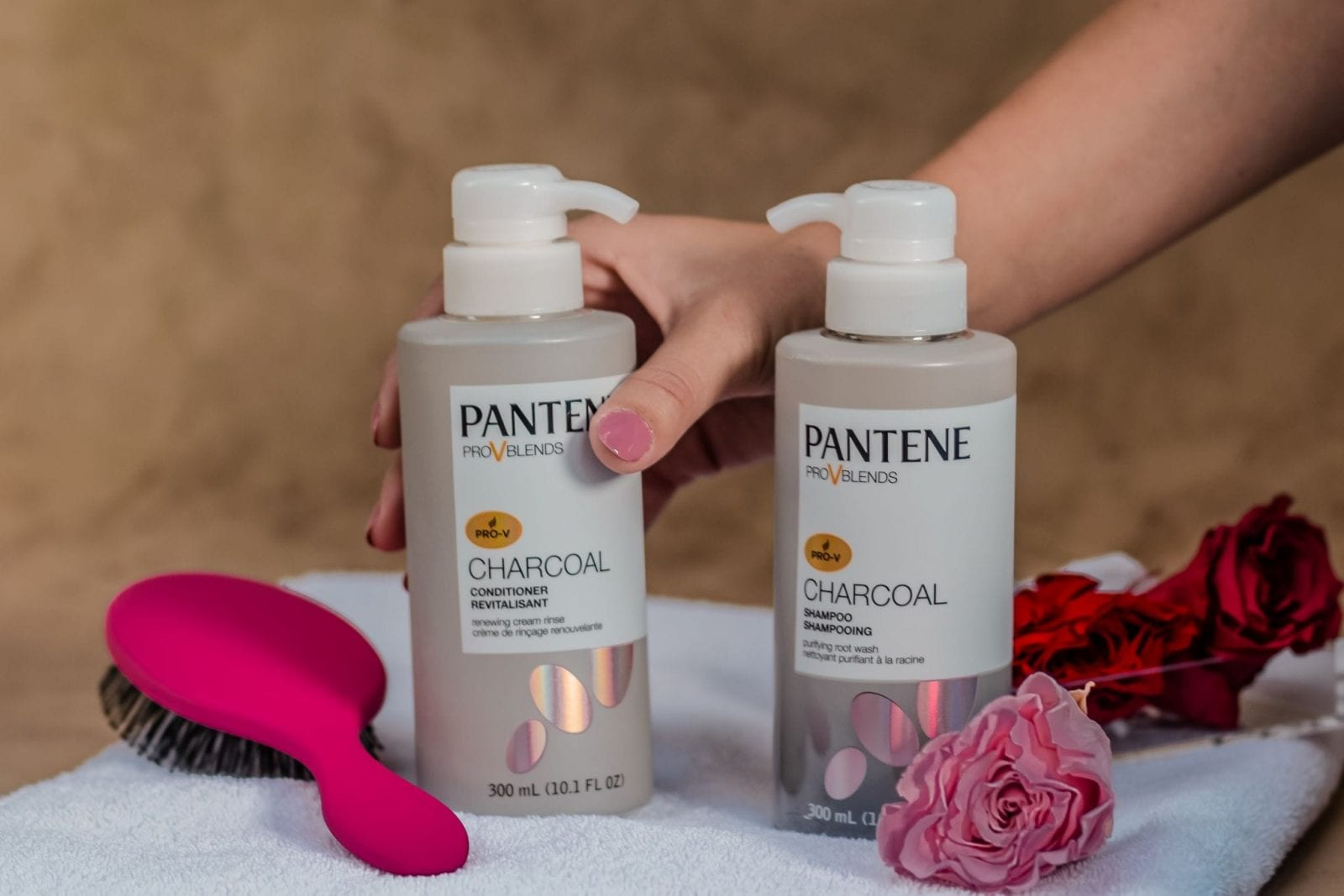 This is a close up of me grabbing for the Pantene Charcoal Shampoo, which is place on a gorgeous towel with roses.