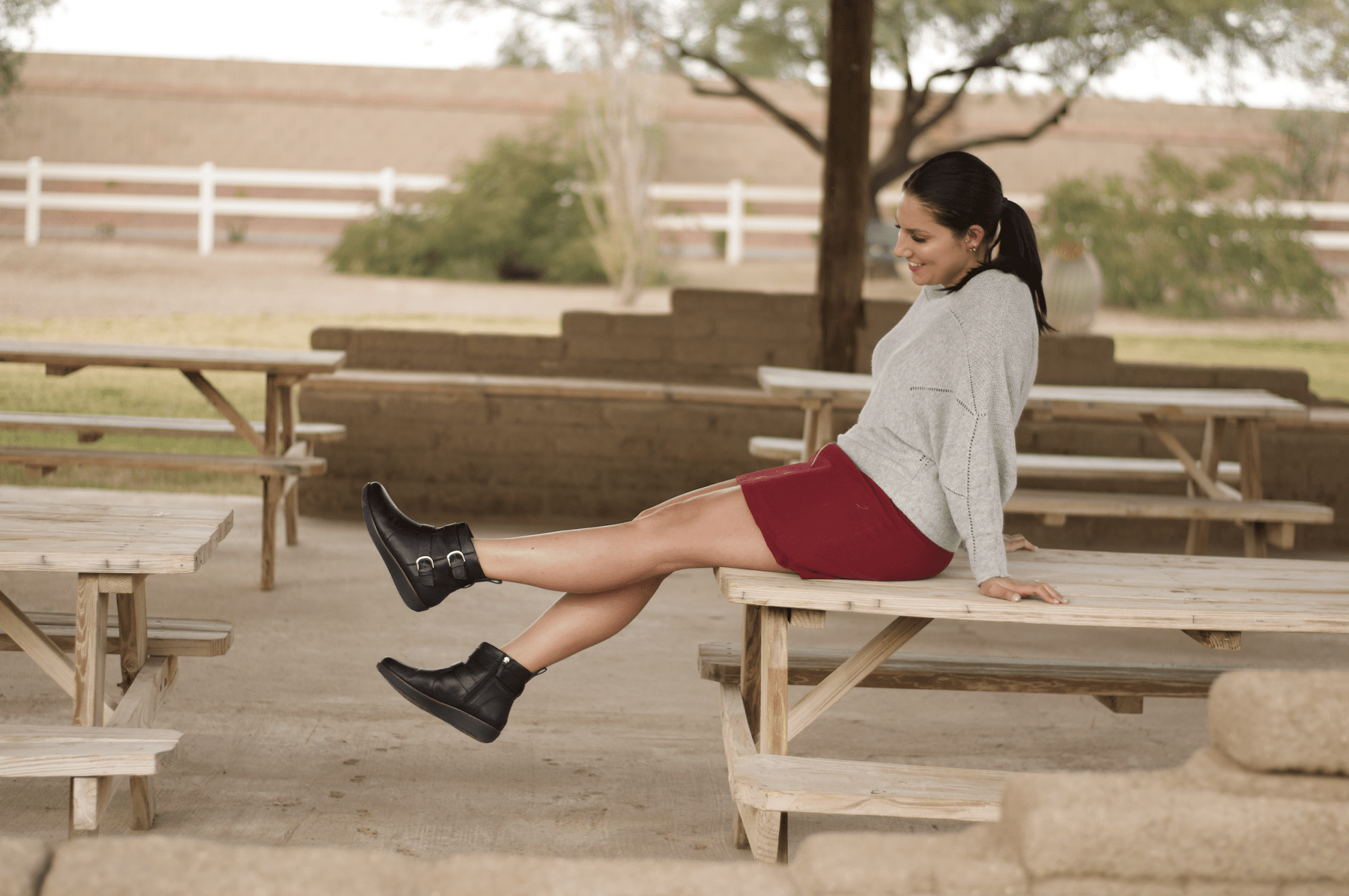 This is a photo of me sitting on a picnic table, with my legs in the air rocking my black booties from FitFlop.