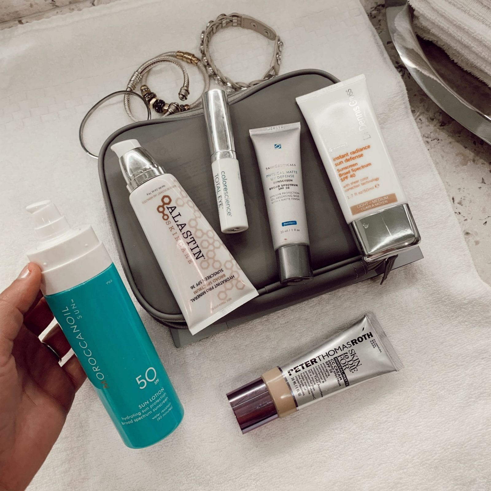 This is a flat lay of my favorite sunscreen products, including Skinceuticals, Dr Dennis Gross, Moroccan Oil, Peter Thomas Roth and Colorscience.