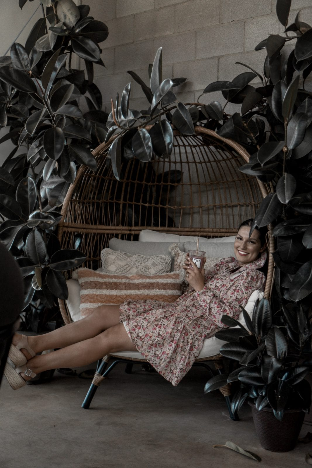 In this photo, I am sitting sideways at Teaspressa in a fun wicker chair surrounded by plants.