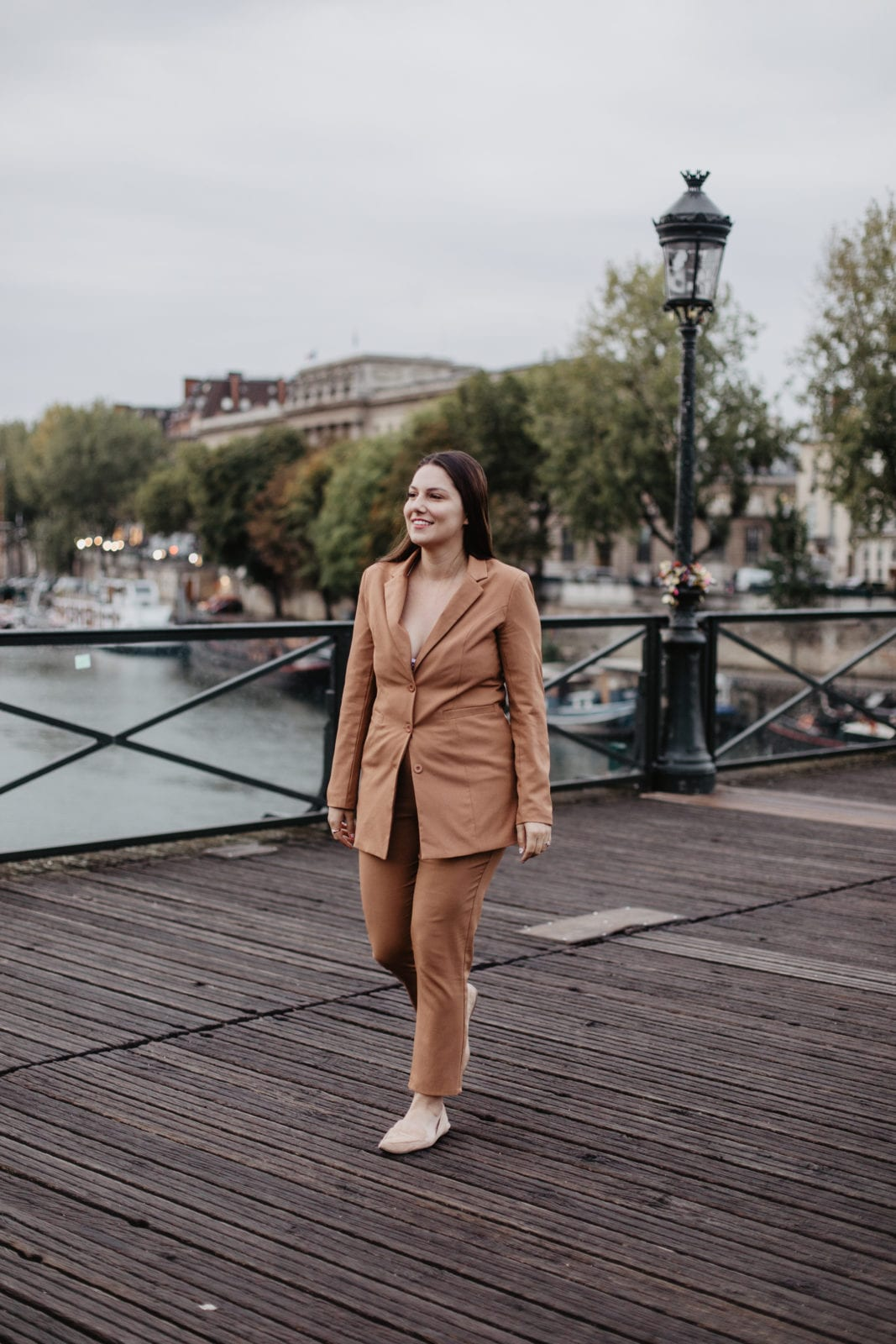 In this photo, I am walking down Pond des Arts in Paris, France while wearing a camel colored full suit from In The Style.