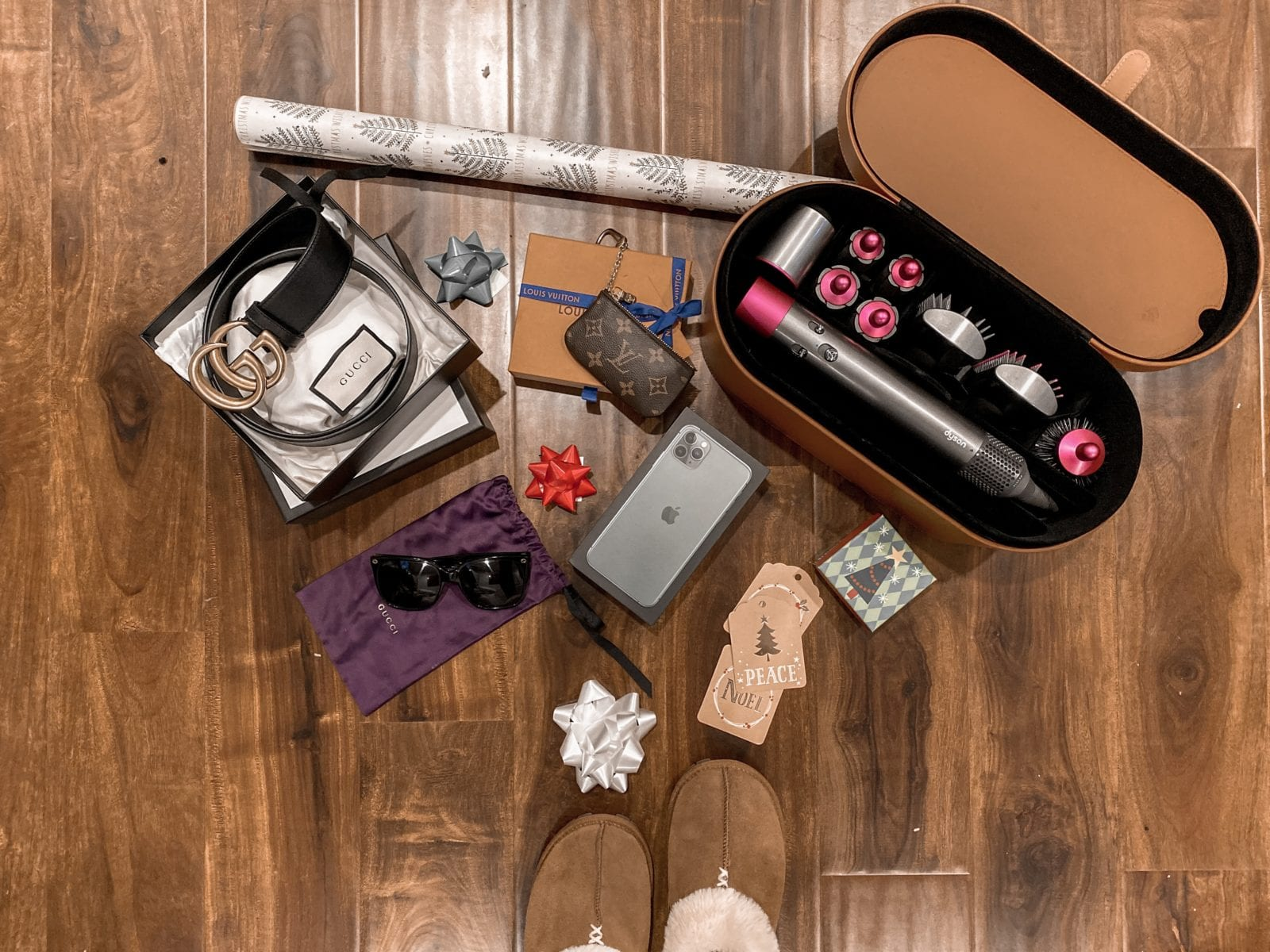 This is a flat lay, including slippers, Dyson dryer, Gucci belt, Gucci sunglasses and more splurge worthy items.