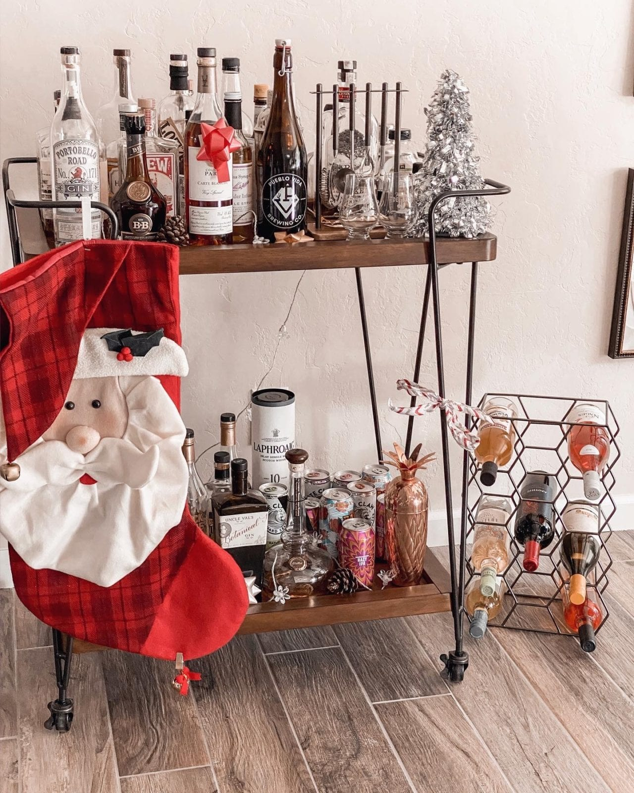I decorated my bar cart for the holidays with a stocking, some flower lights, pinecones and ribbon throughout!