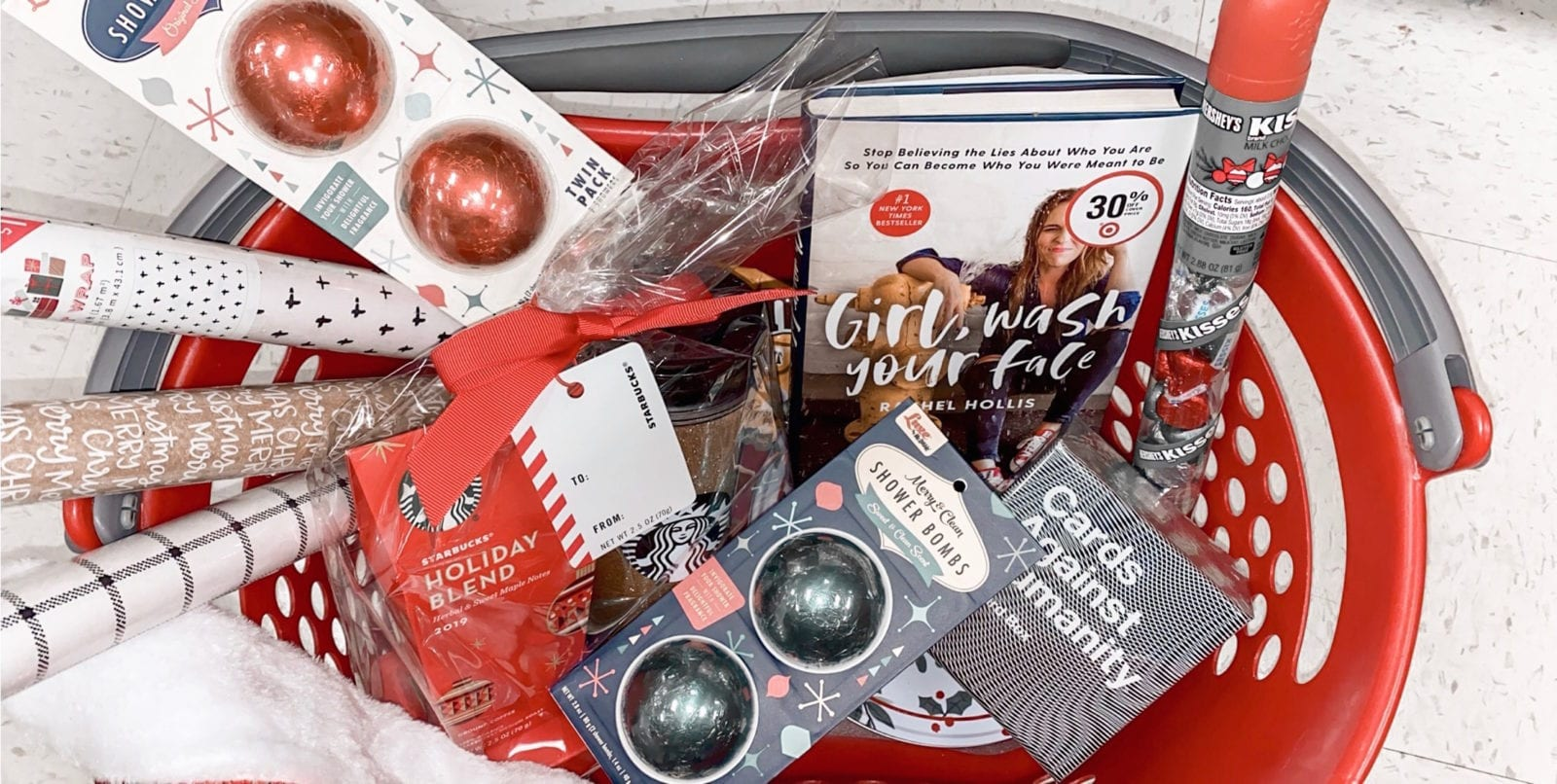 several great white elephant gifts are piled up in a target basket. From holiday glitter bath bombs and cozy socks, to books, card games, and coffee gift sets.