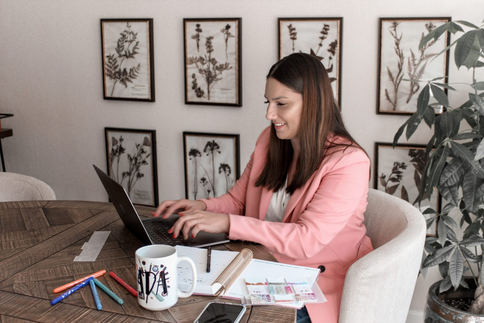 In this image, Adaleta is sitting at her dining room table, writing out her financial goals for 2020. She's utilizing her planner, her computer, and the Lexington Law app on her phone to plan her path to financial freedom.