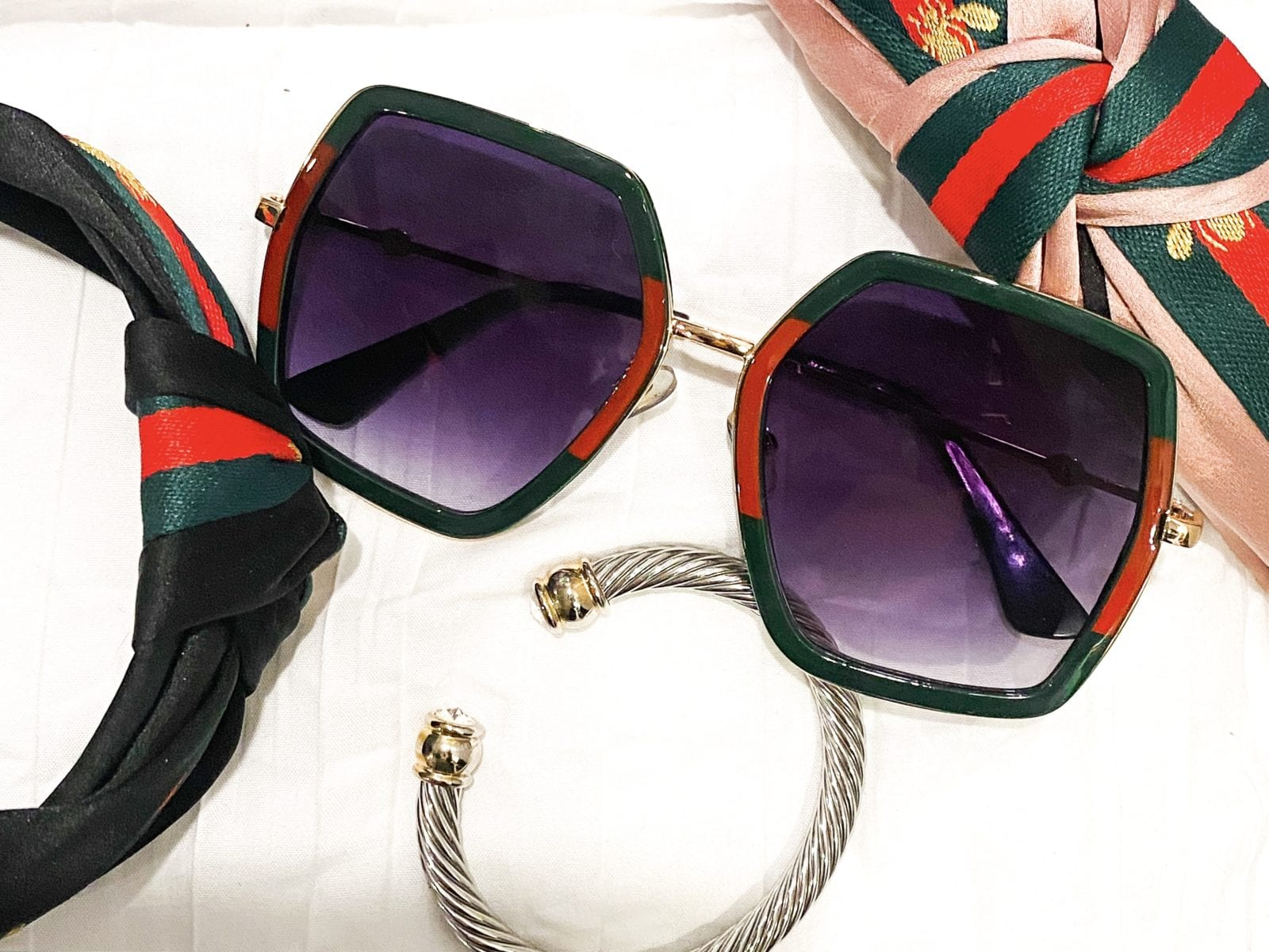 this image is a flat lay of some of the best designer dupes from amazon. In the photo there is a pink and black gucci dupe headband, a pair of gucci dupe sunglasses and a David Yurman dupe bracelet.