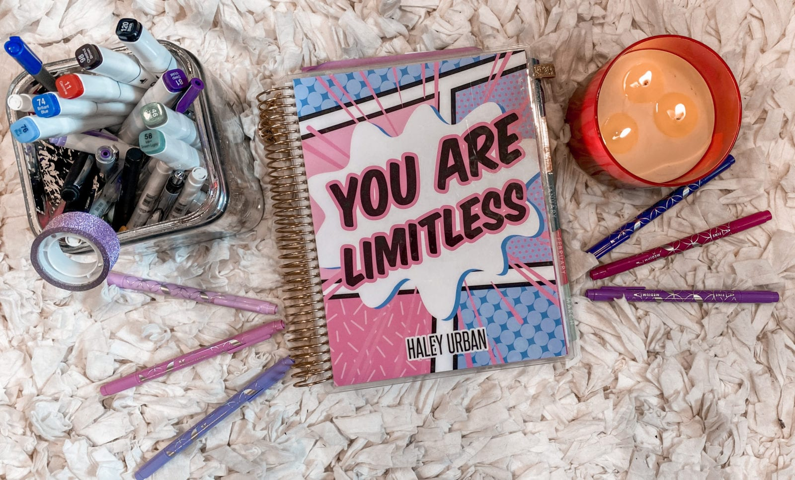 In this image, an Erin Condren life planner is laying next to a 3-wick candle, and a ton of felt-tip markers from Erin Condren.