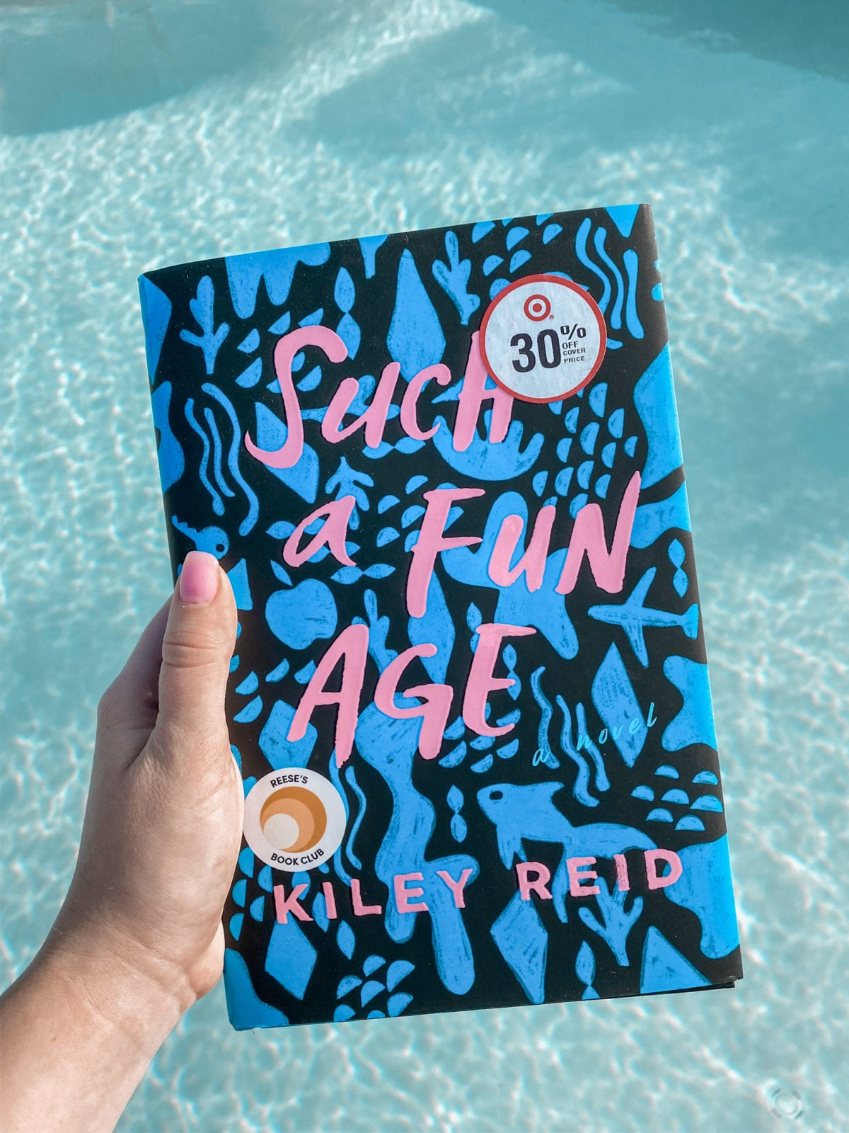 In this image, Haley is sharing one of the books she plans to read in February called, Such a Fun Age by Kiley Reid. The title is very vibrant with bluefish, keys, airplanes, and pink font.