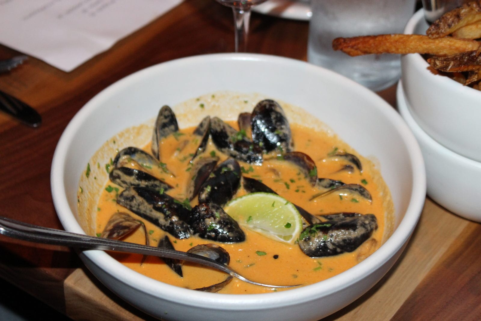 In this image, Adaleta (aka adaatude) is sharing one of her favorite appetizers, the mussels with Thai curry sauce, lemon wedge, herbs, and fries from Commoner and Co in Tucson, Arizona.