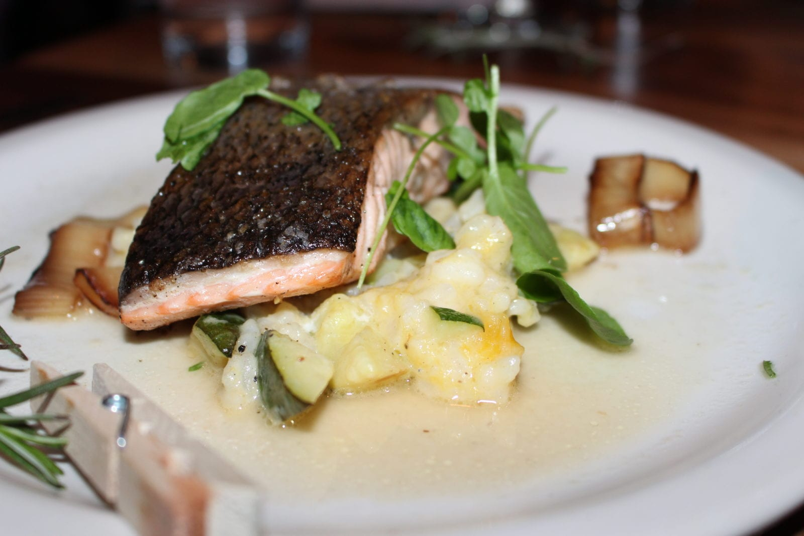 Adaleta is sharing her salmon entree from Commoner & Co located in Tucson, Arizona. The seared salmon is placed on top of winter squash risotto, dill, tarragon nage, and charred leek.