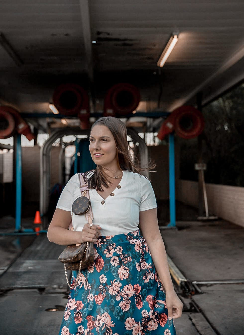 Adaleta Avdic is standing in front of a car wash, while holding her floral maxi skirt in light pink wedges.