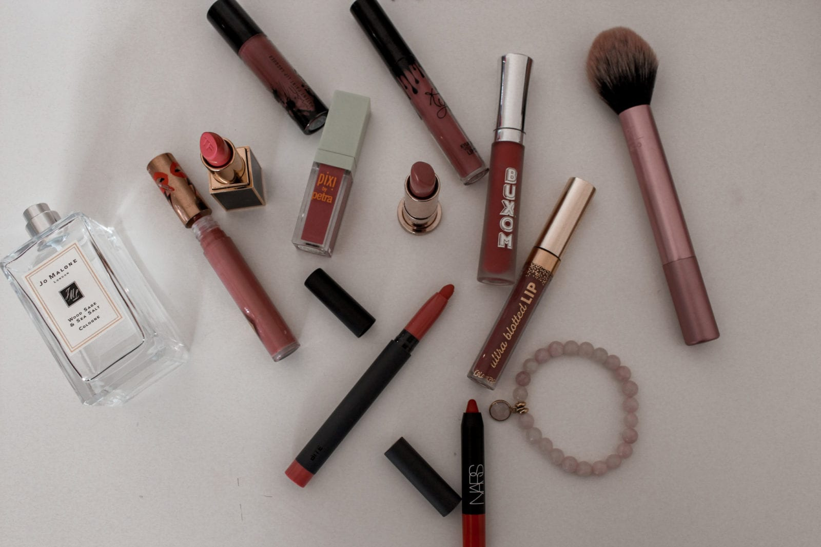 In this image, several of the lip glosses and lipsticks talked about in the post are laying on top of a white surface.