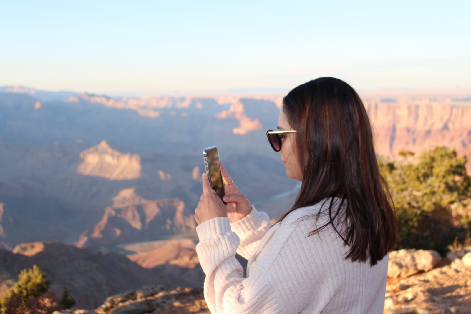 In this photo, Adaleta (aka adaatude online) is holding her phone and capturing video content of the Grand Canyon.